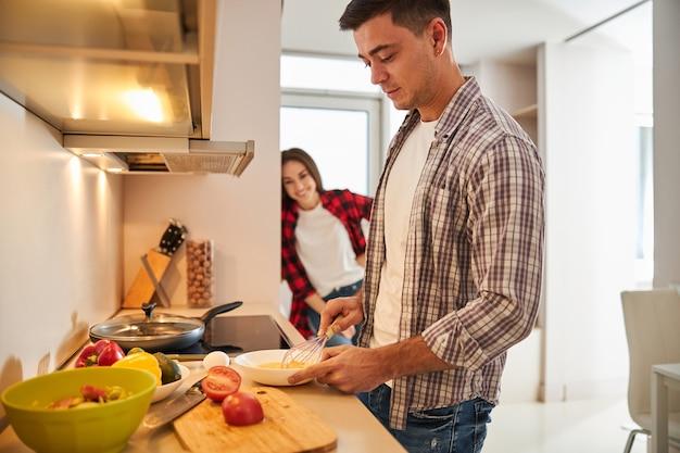 그의 웃는 만족된 배우자를 위해 아침 식사를 만드는 남자