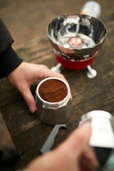 Человек делает кемпинг кофе на открытом воздухе с металлической гейзерной кофеваркой на газовой горелке, шаг за шагом.