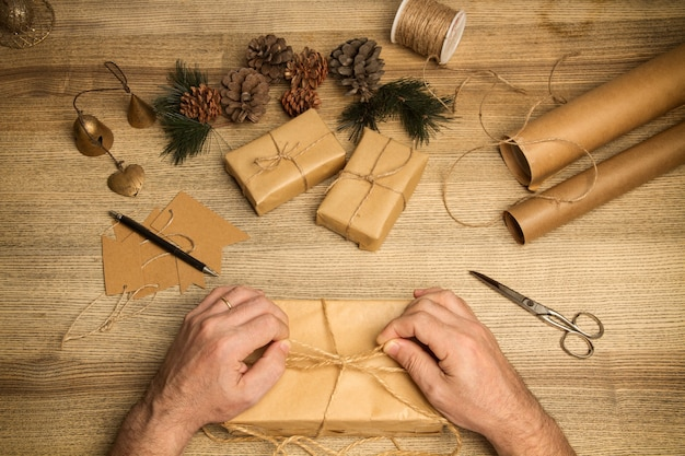 Man making a christmas packages on a wooden table in a top view