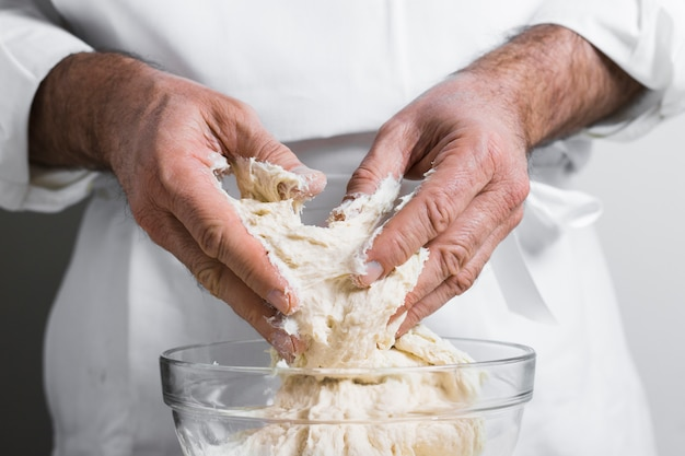 Man making dough from bowl for bread front view
