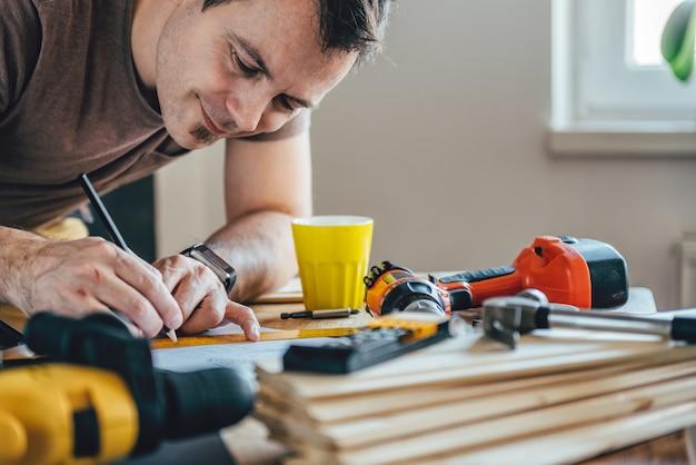 Человек делает проект плана с карандашом на столе