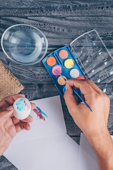 Man making an easter egg with paint on dark wooden background