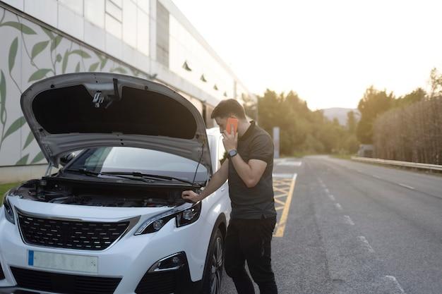 Человек делает экстренный вызов после поломки автомобиля. носит черную одежду. разбитая белая машина с открытым капотом припаркована у дороги