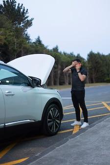 Человек делает экстренный вызов после поломки автомобиля с рукой, закрывающей глаза. находится в черной одежде рядом с разбитой белой машиной с открытым капотом, припаркованной у дороги на фоне деревьев.