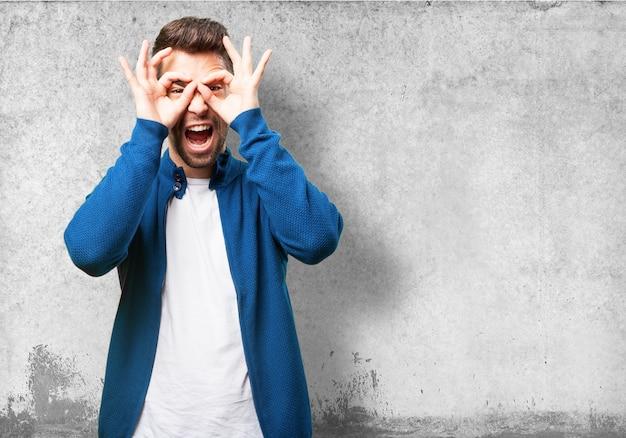 Человек делает очки с его пальцами и с открытым ртом