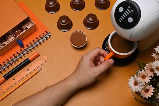 갈색 가죽에 커피 머신으로 뜨거운 커피를 만드는 남자.