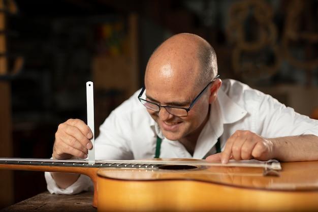 그의 워크샵에서 악기를 만드는 남자