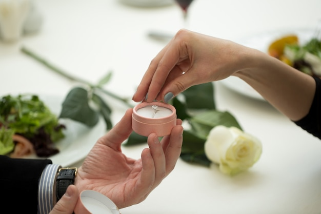 Man making marriage proposal to girlfriend at restaurant, closeup