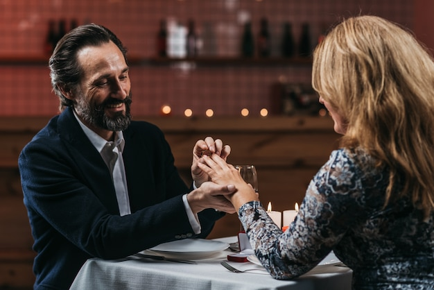 Man making marriage proposal with the ring to his girlfriend and put ring on hand in a restaurant