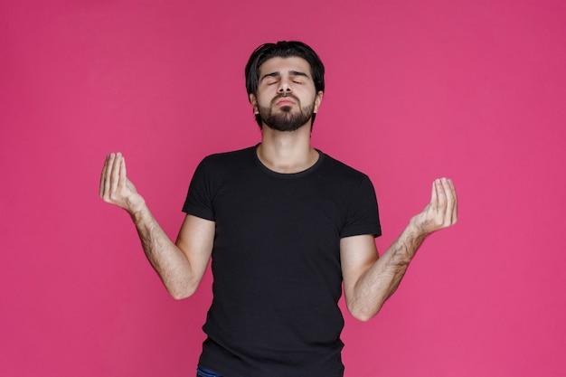 Uomo che fa segni di meditazione o segni di danza indiana in mano.