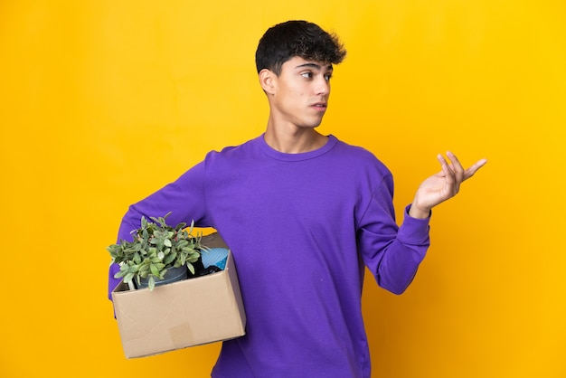 Man making a move while picking up a box full of things extending hands to the side for inviting to come