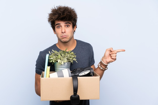 Man making a move while picking up a box full of things pointing to the laterals having doubts