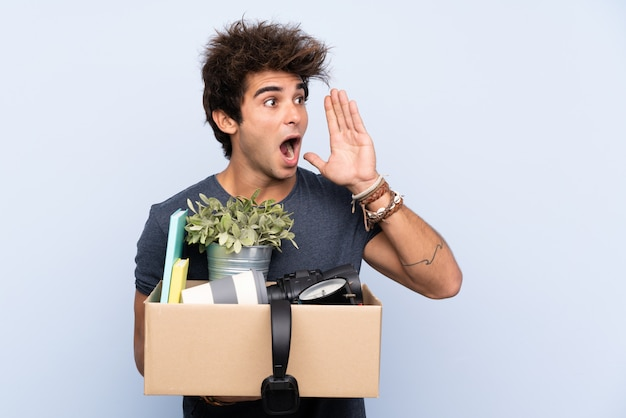 Man making a move while picking up a box full of things shouting with mouth wide open