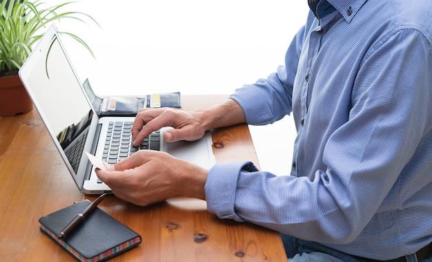 コンピューターの前でオンライン支払いをしている男性。