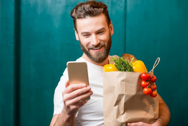 녹색 배경에 건강 식품으로 가득 찬 종이 가방을 들고 스마트 폰으로 온라인 구매를 하는 남자