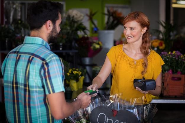 여성 꽃집에 그의 신용 카드로 결제하는 사람
