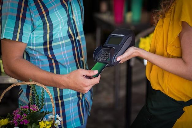 그의 신용 카드로 결제하는 사람