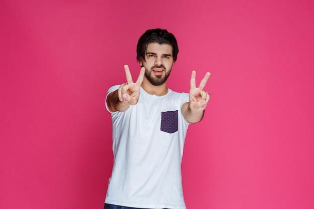 평화와 우정 손 기호를 만드는 남자.