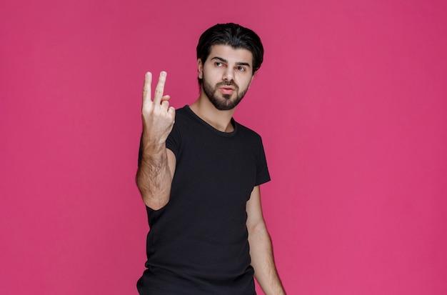 평화 손 기호를 만드는 남자.