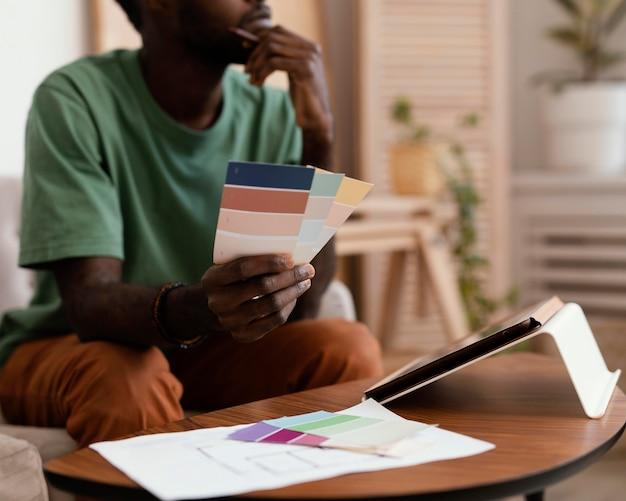 Uomo che fa un piano utilizzando tablet per ridipingere la casa