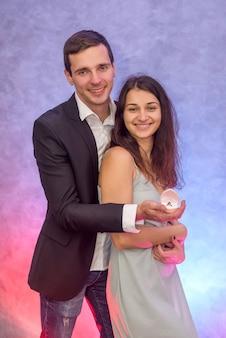 ダイヤモンドで彼女の金の指輪を見せている彼のガールフレンドに提案をしている男