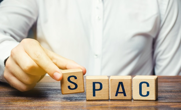 Man making spac word from blocks in a row a easy way stock exchange financial instrument
