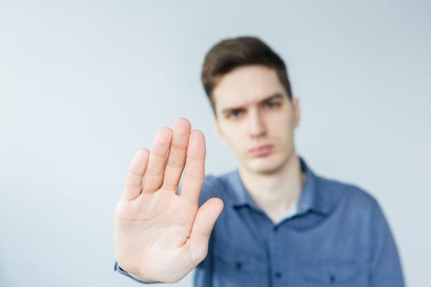 Человек делает стоп сигнал. человек с вытянутой рукой. молодой человек говорит нет