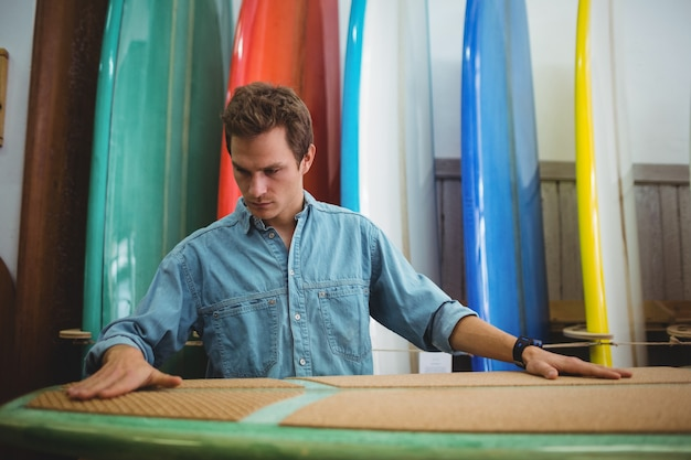 Человек, делающий доску для серфинга
