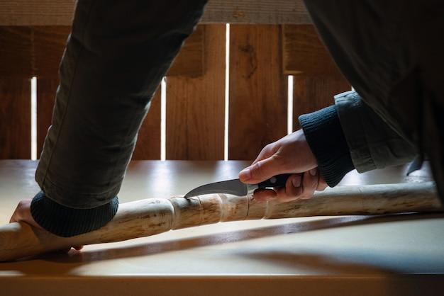 검역 중 실내에서 나무 지팡이를 만드는 남자