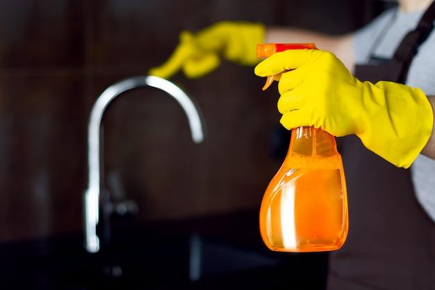 黒いテーブルとキッチンタップを輝くモダンなロフトの金属クロムを洗浄するクリーナーのオレンジ色のボトルと黄色のゴム手袋のクリーニングサービスから男性男性クリーナー手。男は台所を掃除します。