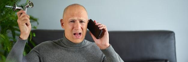 남자 남자 보유 가구 피팅 및 집에서 휴대 전화에 대 한 얘기.