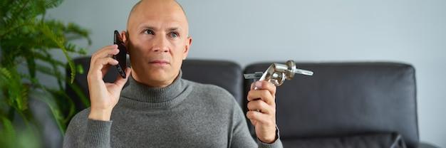 남자 남자 보유 가구 피팅 및 소파에서 휴대 전화에 대 한 얘기.