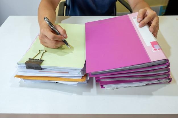 Менеджер человек подписывает бухгалтерскую бумагу с файлом стека на столе
