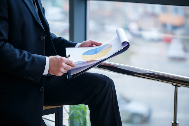 Man managing director leaned on a wooden table in his office near a large window and looks at a successful business development plan.