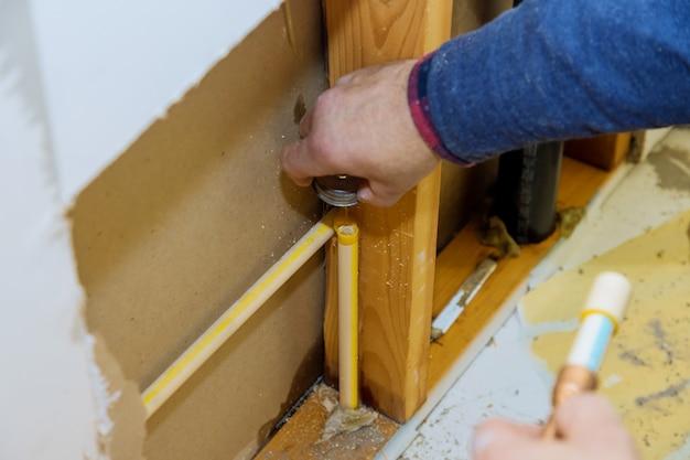 Мужчина вручную отрезает кусок полипропиленовой трубы для прокладки водопровода строящегося нового дома