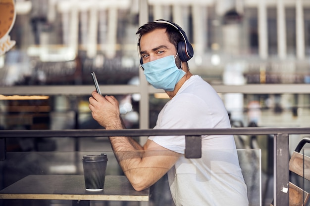 Of a man in mask at caffe with smartphone in headphones