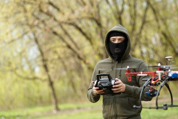 Man in mask flying with the drone. technology thief concept