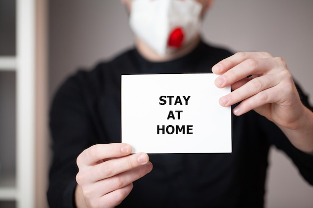 Man in a mask holds a sheet with the inscription stay at home