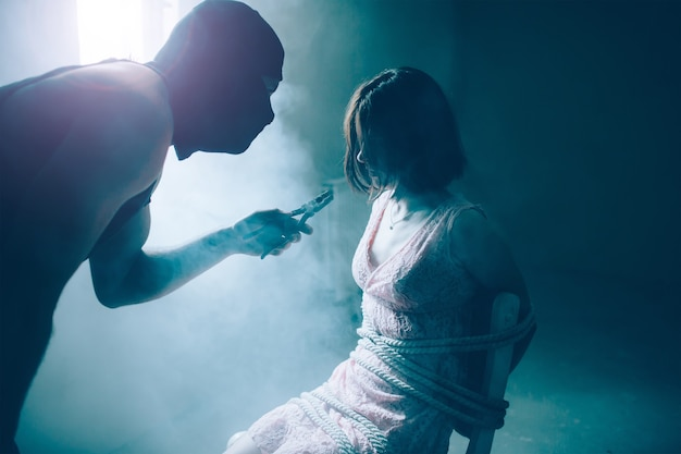 Man in mask is standing close to his victim and looking at her. he is holding pliers in hand. girl is sitting tied to chair. she is tired and exhausted