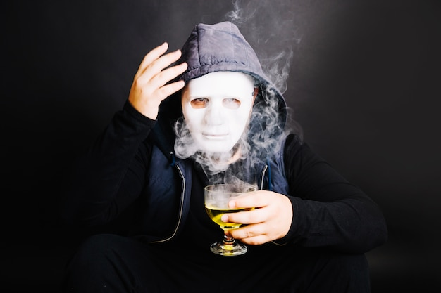 Man in mask with poisonous drink
