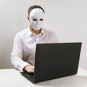 A man in a mask works behind a laptop the concept of anonymity on the internet