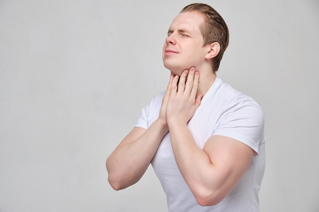 Man massages his neck in pain.