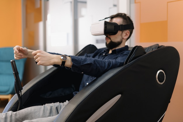 A man in a massaging armchair using vr technology