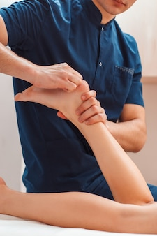 Man massaging female feet close up