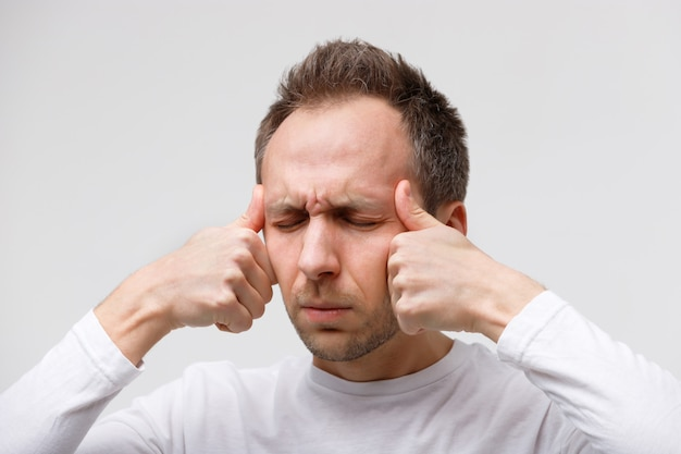 Man massaging his temples, suffering from nervous tension