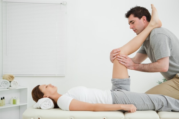 Man massaging a knee while placed it on his shoulder