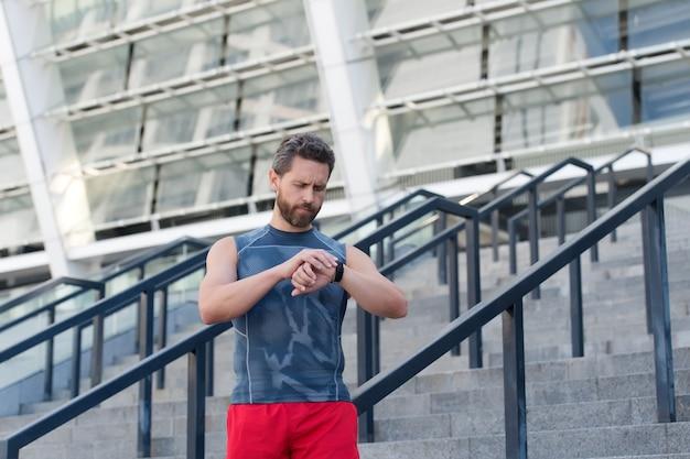 스마트 시계를 사용하는 성숙한 스포츠맨은 건강 마커를 확인합니다.