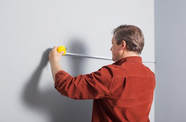 남자는 건설 테이프로 회색 벽을 측정