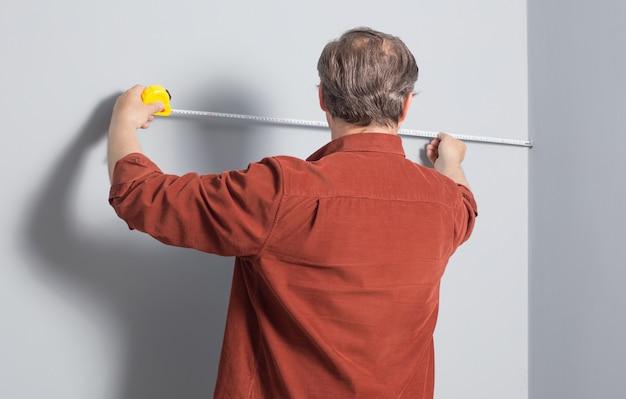男は建設テープで灰色の壁を測定します