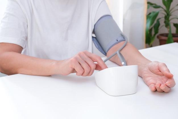 Человек измеряет кровяное давление, белый фон. артериальная гипотензия. рука и тонометр заделывают.